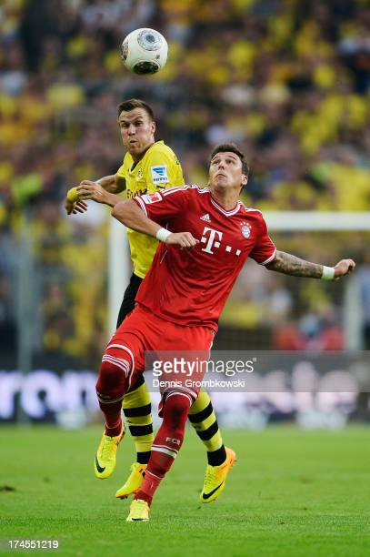 Mario Mandzukic of Bayern Muenchen is challenged by Kevin Grosskreutz of Borussia Dortmund during the DFL Supercup match between Borussia Dortmund...