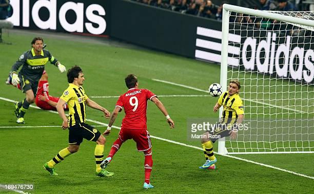 Mario Mandzukic of Bayern Muenchen scores a goal past Marcel Schmelzer of Borussia Dortmund and Mats Hummels of Borussia Dortmund during the UEFA...