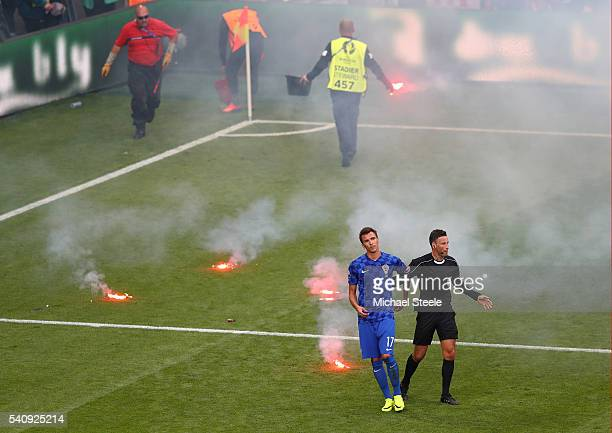 Mario Mandzukic of Croatia and Mark Clattenburg walk on as flairs are thrown onto the pitch during the UEFA EURO 2016 Group D match between Czech...