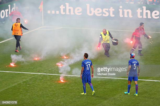 Mario Mandzukic of Croatia and Vedran Corluka of Croatia look on as fire marshal's take flares from the pitch during the UEFA EURO 2016 Group D match...