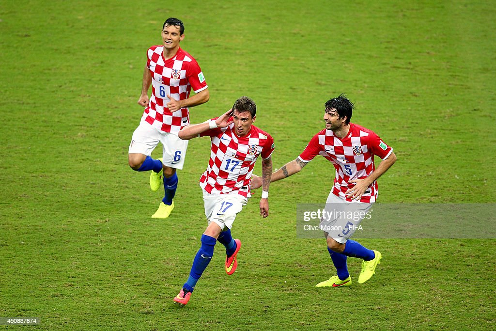 <a gi-track='captionPersonalityLinkClicked' href=/galleries/search?phrase=Mario+Mandzukic&family=editorial&specificpeople=4476149 ng-click='$event.stopPropagation()'>Mario Mandzukic</a> (C) of Croatia celebrates scoring his team's third goal with his teammates <a gi-track='captionPersonalityLinkClicked' href=/galleries/search?phrase=Dejan+Lovren&family=editorial&specificpeople=5577379 ng-click='$event.stopPropagation()'>Dejan Lovren</a> (L) and <a gi-track='captionPersonalityLinkClicked' href=/galleries/search?phrase=Vedran+Corluka&family=editorial&specificpeople=1462334 ng-click='$event.stopPropagation()'>Vedran Corluka</a> (R) during the 2014 FIFA World Cup Brazil Group A match between Cameroon and Croatia at Arena Amazonia on June 18, 2014 in Manaus, Brazil.