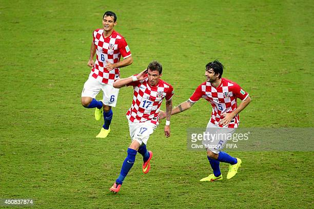Mario Mandzukic of Croatia celebrates scoring his team's third goal with his teammates Dejan Lovren and Vedran Corluka during the 2014 FIFA World Cup...