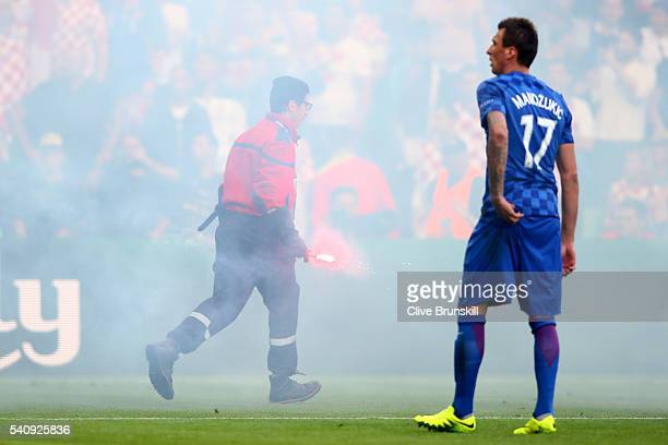 Mario Mandzukic of Croatia looks on as flares are thrown onto the picth during the UEFA EURO 2016 Group D match between Czech Republic and Croatia at...