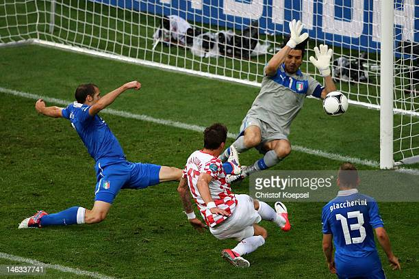 Mario Mandzukic of Croatia scores the opening goal past Gianluigi Buffon of Italy during the UEFA EURO 2012 group C match between Italy and Croatia...