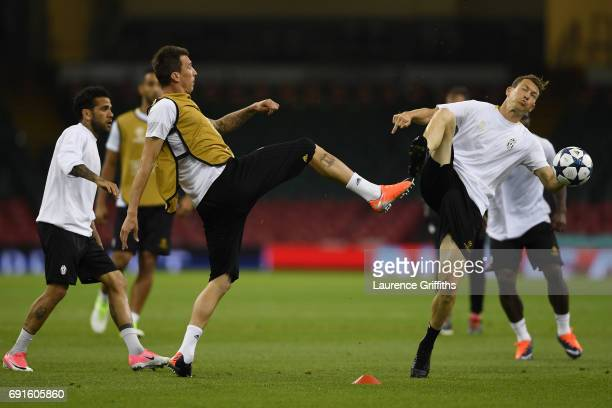 Mario Mandzukic of Juventus and Stephan Lichtsteiner of Juventus battle for possession during a Juventus training session prior to the UEFA Champions...
