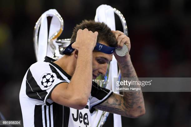 Mario Mandzukic of Juventus collects his runners up medal after the UEFA Champions League Final between Juventus and Real Madrid at National Stadium...