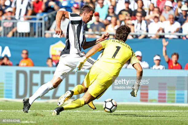 Mario Mandzukic of Juventus dribbles past Alisson Becker of Roma to score during the International Champions Cup 2017 match at Gillette Stadium on...