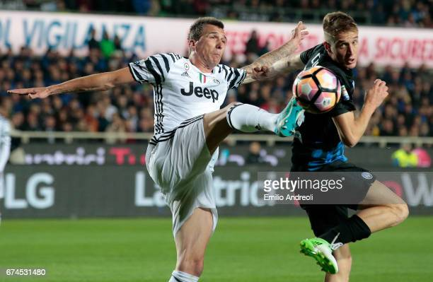 Mario Mandzukic of Juventus FC competes for the ball with Andrea Conti of Atalanta BC during the Serie A match between Atalanta BC and Juventus FC at...