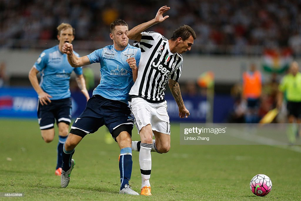 Mario Mandzukic (R) of Juventus FC contests the ball against Stefan De Vrij (C) of Lazio during the Italian Super Cup final football match between Juventus and Lazio at Shanghai Stadium on August 8, 2015 in Shanghai, China.
