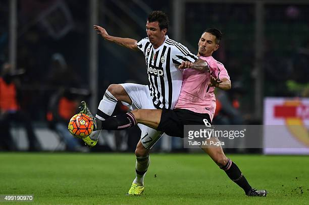 Mario Mandzukic of Juventus is challenged by Edoardo Goldaniga of Palermo during the Serie A match between US Citta di Palermo and Juventus FC at...