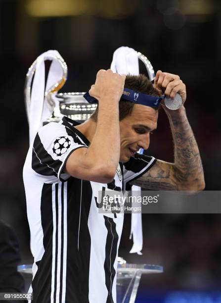 Mario Mandzukic of Juventus puts on his runners up medal after the UEFA Champions League Final between Juventus and Real Madrid at National Stadium...