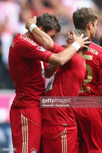 Mario Mandzukic of Muenchen celebrates scoring the opening goal with his team mate Xherdan Shaqiri during the Bundesliga match between FC Bayern...