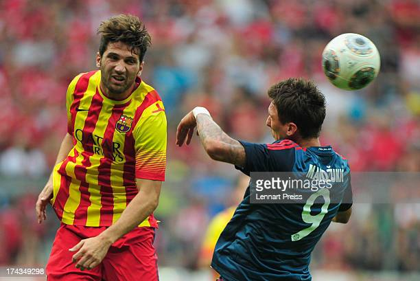 Mario Mandzukic of Muenchen challenges Carles Planas of Barcelona during the Uli Hoeness Cup match between FC Bayern Muenchen and FC Barcelona at...