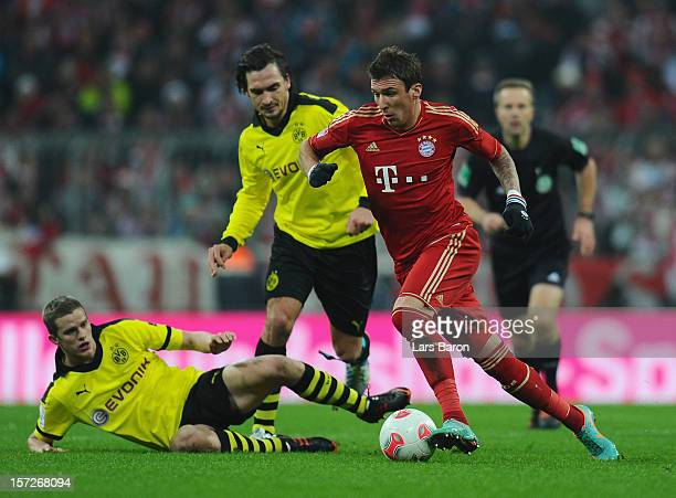 Mario Mandzukic of Muenchen challenges Sven Bwender and Mats Hummels of Dortmund during the Bundesliga match between Bayern Muenchen and Borussia...