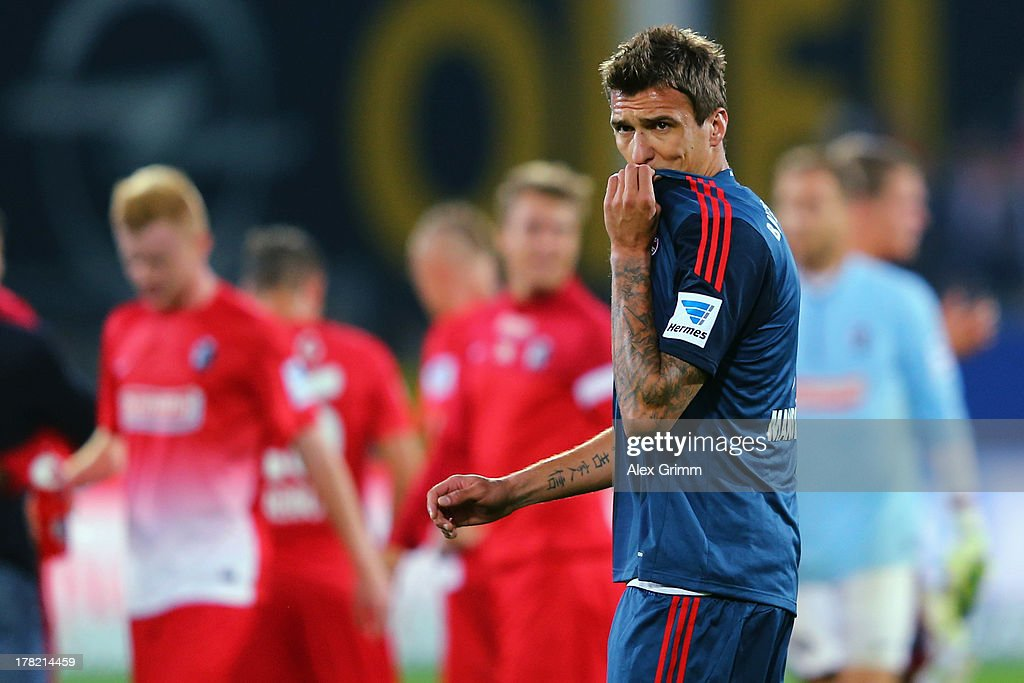 <a gi-track='captionPersonalityLinkClicked' href=/galleries/search?phrase=Mario+Mandzukic&family=editorial&specificpeople=4476149 ng-click='$event.stopPropagation()'>Mario Mandzukic</a> of Muenchen reacts as players of Freiburg celebrate after the Bundesliga match between SC Freiburg and FC Bayern Muenchen at MAGE SOLAR Stadium on August 27, 2013 in Freiburg im Breisgau, Germany.