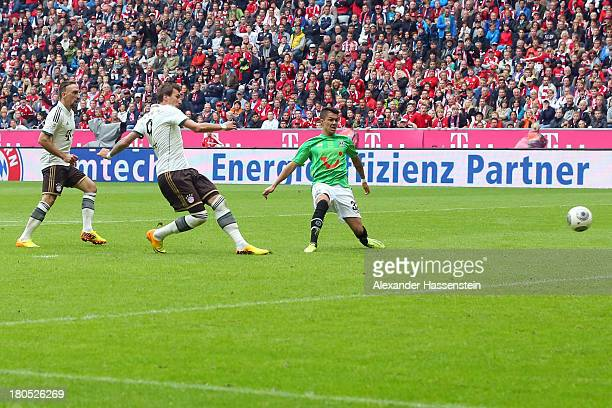 Mario Mandzukic of Muenchen scores the opening goal against Leonardo Bittencourt of Hannover during the Bundesliga match between FC Bayern Muenchen...