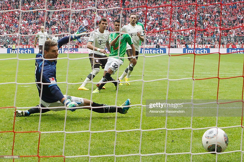 Mario Mandzukic of Muenchen scores the opening goal against Leonardo Bittencourt of Hannover and his keeper RonRobert Zieler during the Bundesliga...
