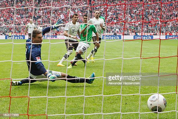 Mario Mandzukic of Muenchen scores the opening goal against Leonardo Bittencourt of Hannover and his keeper RonRobert Zieler during the Bundesliga...