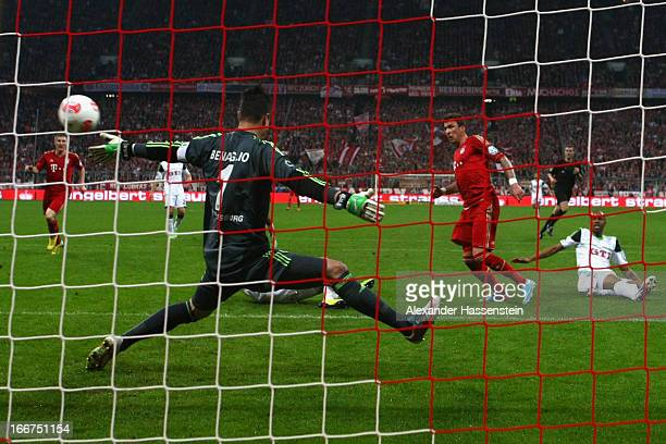 Mario Mandzukic of Muenchen scores the opening goal against Naldo of Wolfsburg and his keeper Diego Benaglio during the DFB Cup Semi Final match...