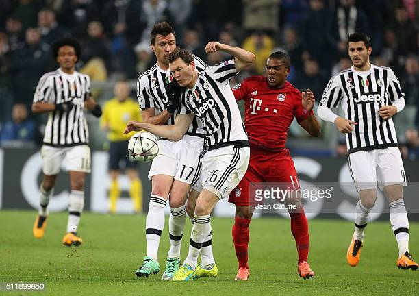 Mario Mandzukic Stephan Lichtsteiner of Juventus and Douglas Costa of Bayern Muenchen in action during the UEFA Champions League Round of 16 first...