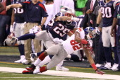 Mario Manningham of the New York Giants catches a 38 yard pass from Eli Manning over Patrick Chung and Sterling Moore of the New England Patriots in...