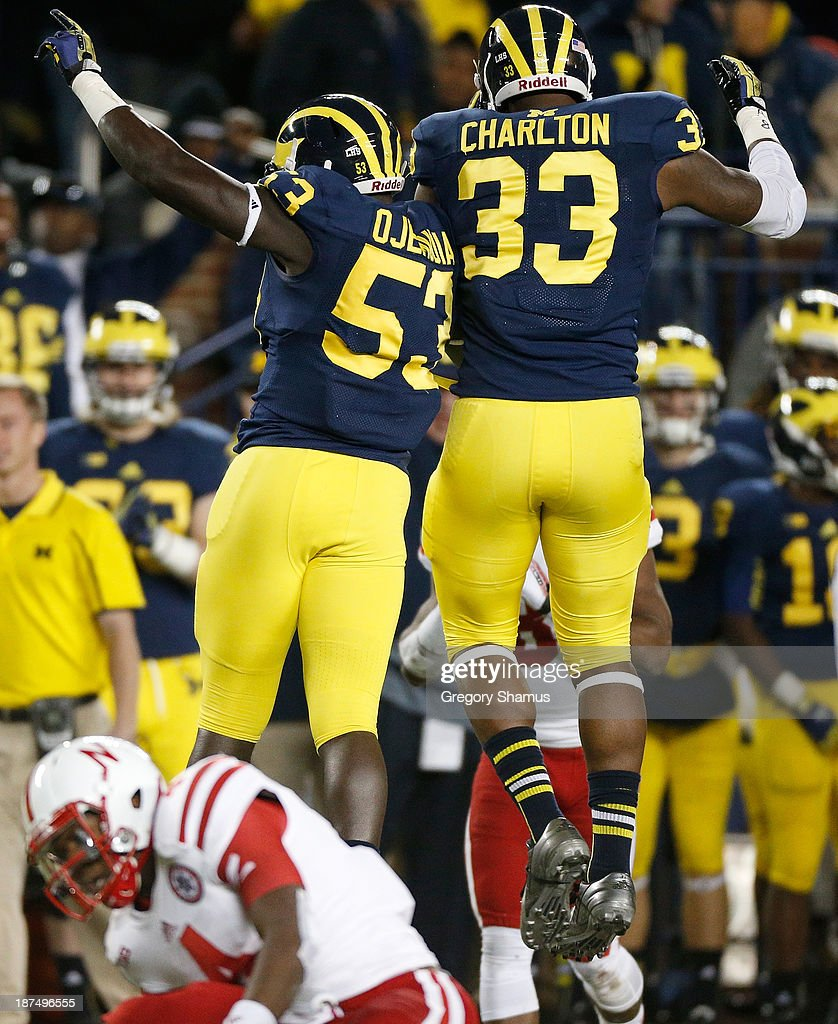 Mario Ojemudia #53 and Taco Charlton #33 of the Michigan Wolverines celebrate a sack of Tommy Armstrong Jr. #4 of the Nebraska Cornhuskers in the second half at Michigan Stadium on November 9, 2013 in Ann Arbor, Michigan.