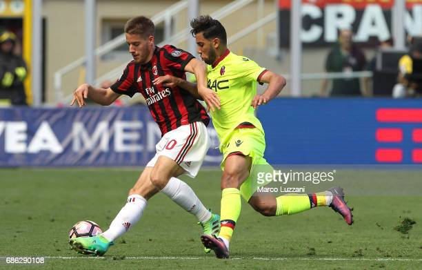 Mario Pasalic of AC Milan is challenged by Saphir Sliti Taider of Bologna FC during the Serie A match between AC Milan and Bologna FC at Stadio...