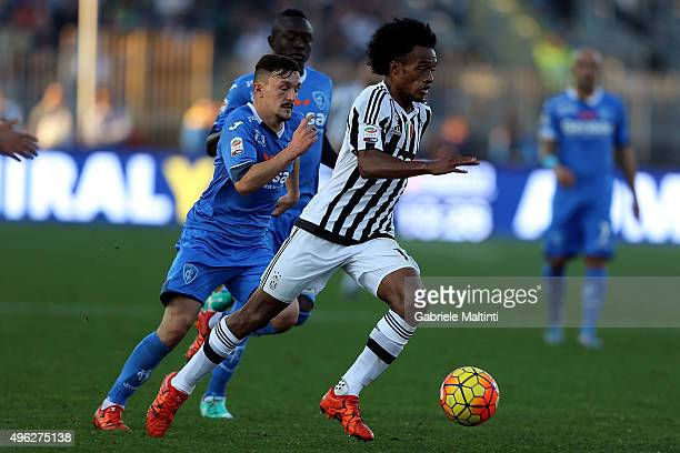 Mario Rui of Empoli FC battles for the ball with Guillermo Cuadrado of Juventus FC during the Serie A match between Empoli FC and Juventus FC at...