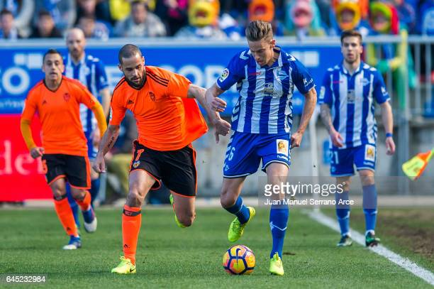 Mario Suarez of Valencia CF duels for the ball with Marcos Llorente of Deportivo Alaves during the La Liga match between Deportivo Alaves and...