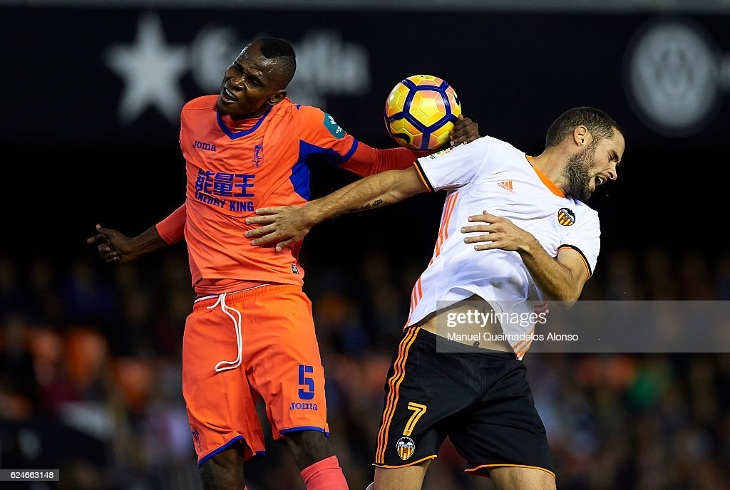 Mario Suarez (R) of Valencia competes for the ball with Uche Henry-Agbo of Granada during the La Liga match between Valencia CF and Granada CF at Mestalla Stadium on November 20, 2016 in Valencia, Spain.