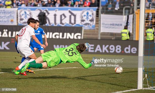 Mario Vrancic of SV Darmstadt 98 scores the first goal for his team against Marwin Hitz of FC Augsburg during the first bundesliga match between SV...
