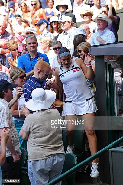 Marion Bartoli of France climbs down from her box as she celebrates victory during the Ladies' Singles final match against Sabine Lisicki of Germany...