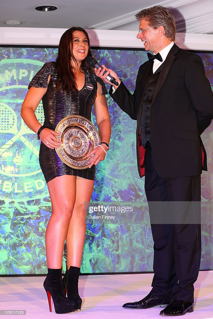 Marion Bartoli of France holds the Venus Rosewater Dish trophy as she is interviewed by Andrew Castle at the Wimbledon Championships 2013 Winners...