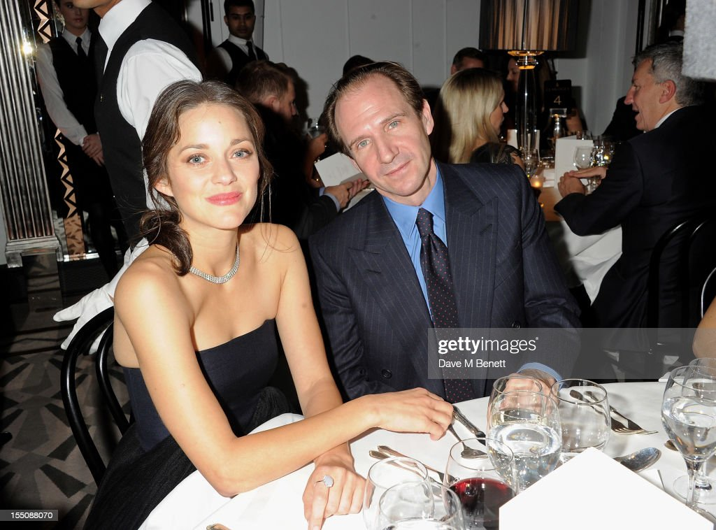 (MANDATORY CREDIT PHOTO BY DAVE M BENETT/GETTY IMAGES REQUIRED) Marion Cotillard (L) and Ralph Fiennes attend the Harper's Bazaar Women of the Year Awards 2012, in association with Estee Lauder, Harrods and Tiffany & Co., at Claridge's Hotel on October 31, 2012 in London, England.