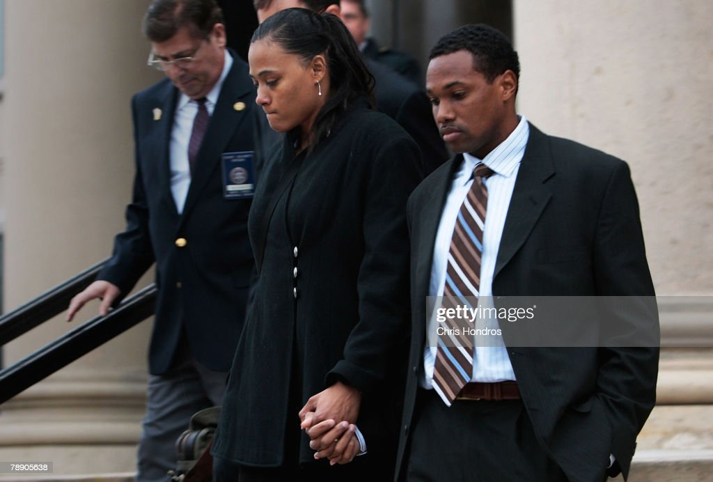 Marion Jones (L) holds hands with her husband Obadele Thompson as she leaves court January 11, 2008 in White Plains, New York. Marion Jones was sentenced to six months in prison for lying about using steroids during her athletic career and a check-fraud scam.