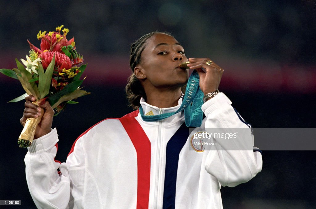 Marion Jones of the United States kisses her gold medal after winning for the womens 100 meter during the Olympic Games in Sydney, Australia at the Olympic Stadium on September 23, 2000. (Photo by: Mike Powell/Getty Images).