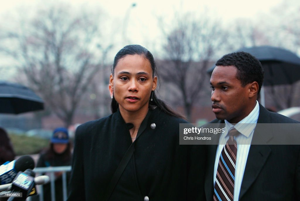 Marion Jones (L) stands with her husband Obadele Thompson after she leaves court January 11, 2008 in White Plains, New York. Marion Jones was sentenced to six months in prison for lying about using steroids during her athletic career and a check-fraud scam.