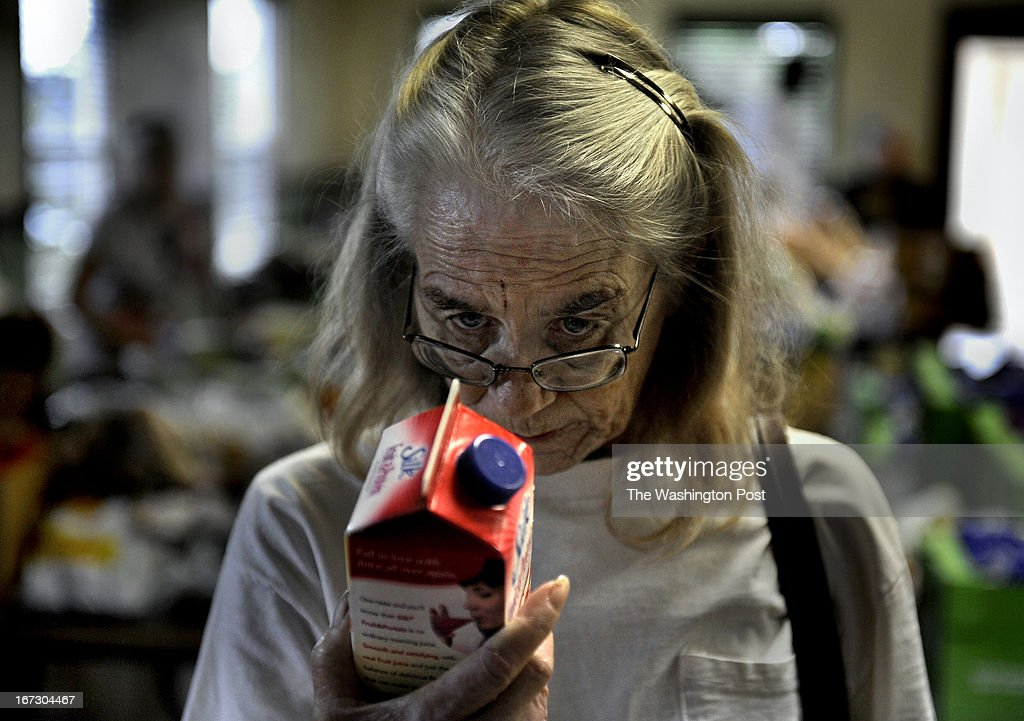 Marion Mattrazzo checks the expiration date on some soy milk at a food pantry in Hobe Sound. Scores of locals waited to get a box of food but senior citizens with a number got to retrieve food first. Mattrazzo, 54, suffers from Cirrhosis of the Liver and lives on about $7,000 per year. She signed up for the SNAP program because what little income she has goes for medical related expenses (she's too young to be eligible for Medicare). She once had a vibrant construction company that suffered badly with the housing collapse in Florida. Adding to her difficulty was that her husband died two years ago. She now rents (for $200 a month) a 100 square foot shack that was tacked onto a garage. The SNAP program is a huge help to her but because she has no stove, she has to buy a lot of microwaveable foods. She's been feeling depressed of late about her current circumstances, 'I'm just existing at this point,' she said. Many low-income seniors qualify to participate in the S.N.A.P. (food stamps) program but do not receive the benefit, often because they are too proud or unaware of it. Photo by Michael S. Williamson/The Washington Post via Getty Images