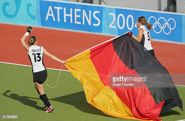 Marion Rodewald and Heike Laetzsch of the German ladies hockey team celebrate with the German flag after victory over Korea during the women's field...