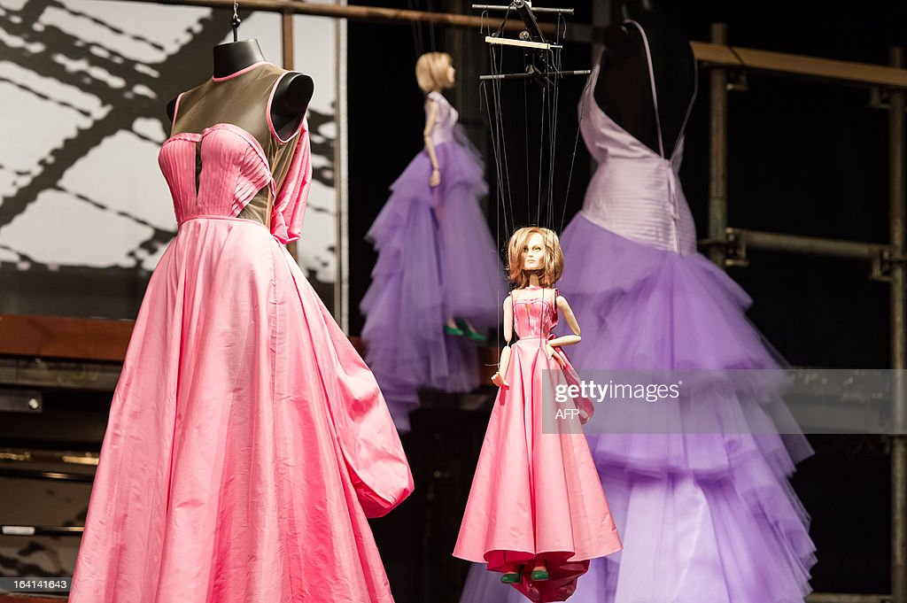 A marionette is seen next to a creation by Fause Haten during the Sao Paulo Fashion Week 2013 Summer collections presentation, in Sao Paulo, Brazil, on March 20, 2013. Real size collections are also showed after the show. AFP PHOTO / Yasuyoshi CHIBA