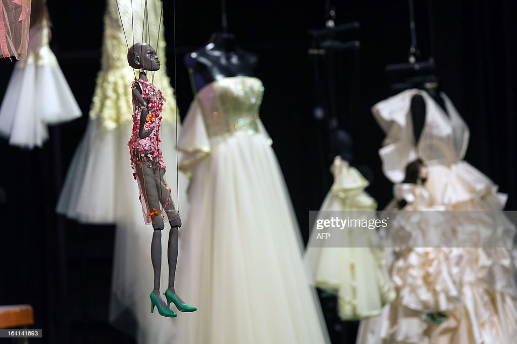 A marionette is seen next to creations by Fause Haten during the Sao Paulo Fashion Week 2013 Summer collections presentation, in Sao Paulo, Brazil, on March 20, 2013. Real size collections are also showed after the show. AFP PHOTO / Yasuyoshi CHIBA