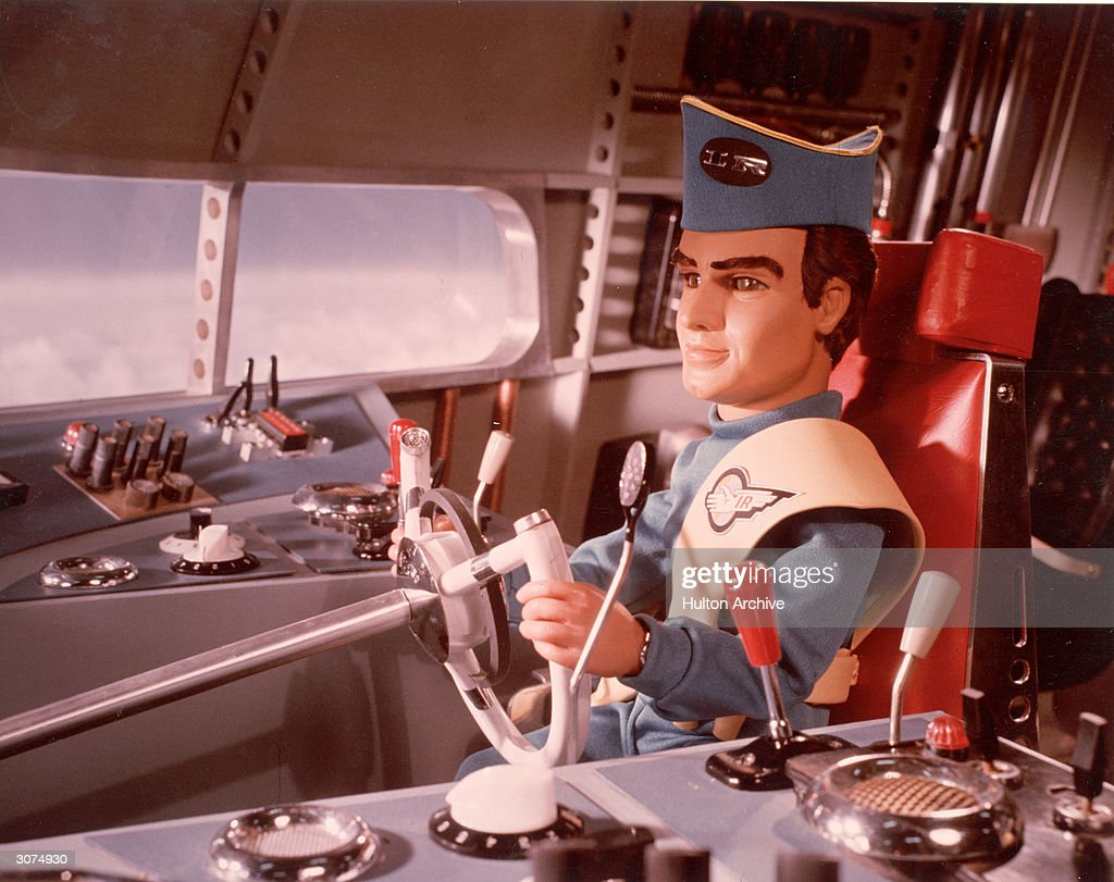 A marionette pilot in uniform steers a vehicle in a still from the television science fiction series, 'Thunderbirds,' circa 1965.