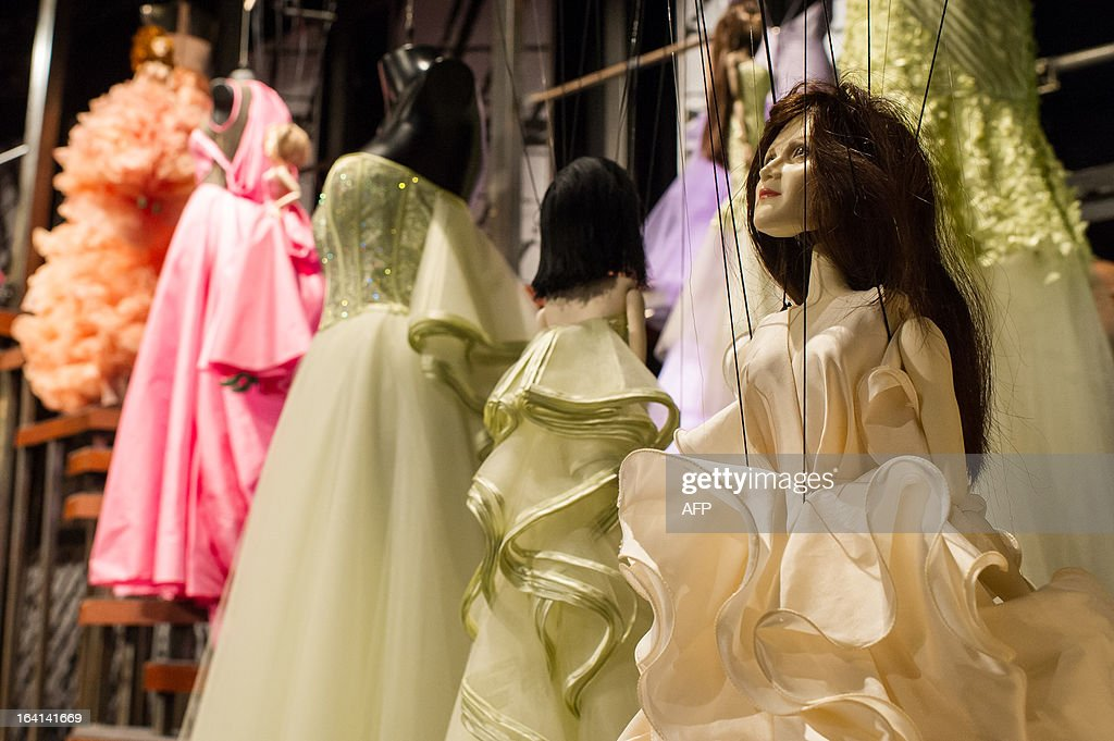 Marionettes are seen next to creations by Fause Haten during the Sao Paulo Fashion Week 2013 Summer collections presentation, in Sao Paulo, Brazil, on March 20, 2013. Real size collections are also showed after the show. AFP PHOTO / Yasuyoshi CHIBA