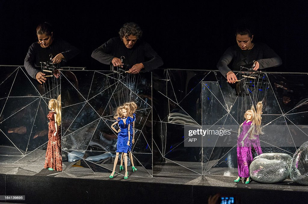Marionettes present creations by Fause Haten during the Sao Paulo Fashion Week 2013 Summer collections, in Sao Paulo, Brazil, on March 20, 2013. Real size collections are also showed after the show. AFP PHOTO / Yasuyoshi CHIBA
