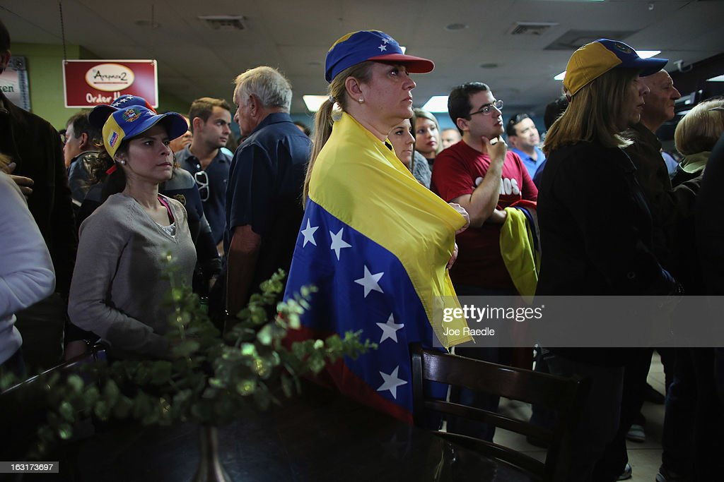 Marisa Perez is wrapped in a Venezuelan flag as she and others listen to what is being said on a television set reporting on the death of Venezuelan president Hugo Chavez, at El Arepazo 2 a restaurant in the heart of a neighborhood that has the largest concentration of Venezuelans in the U.S. on March 5, 2013 in Doral, Florida. The Venezuelan government announced today that Hugo Chavez lost his battle with cancer.