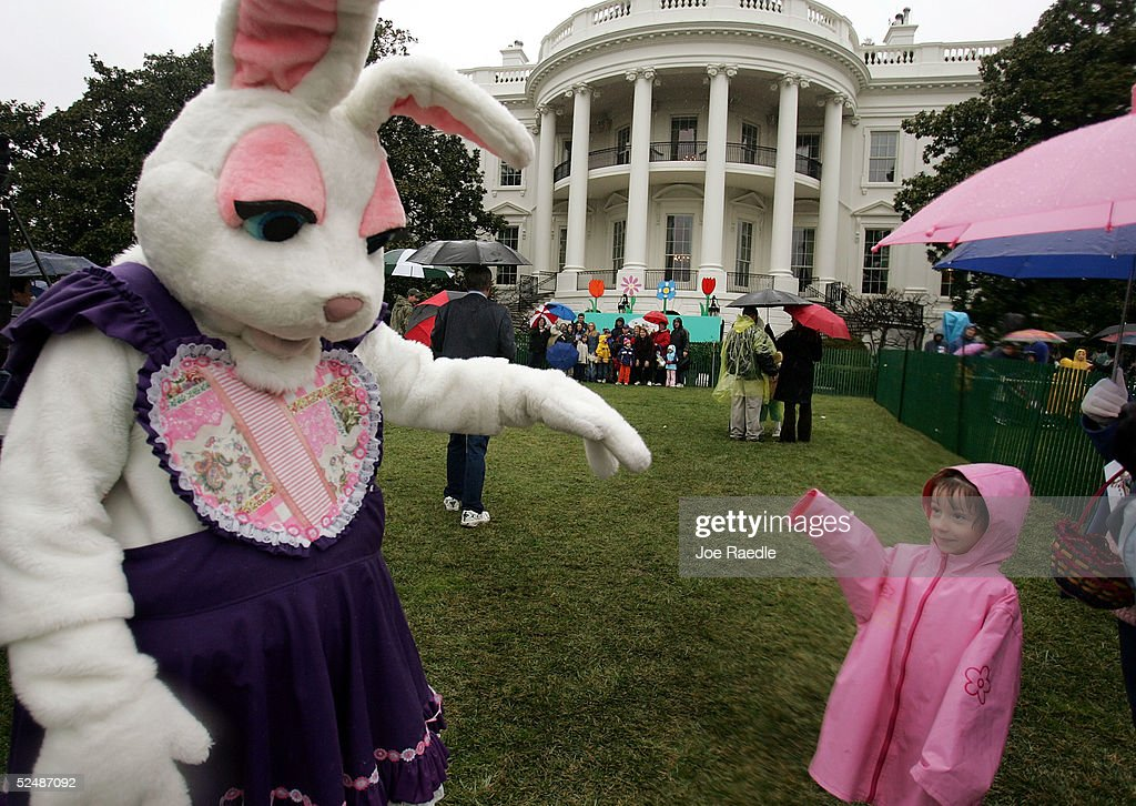 Marisa Pitre from Bowie Maryland waves to a person dressed as an Easter Bunny during the Easter Egg roll March 28 2005 on the White House's South...