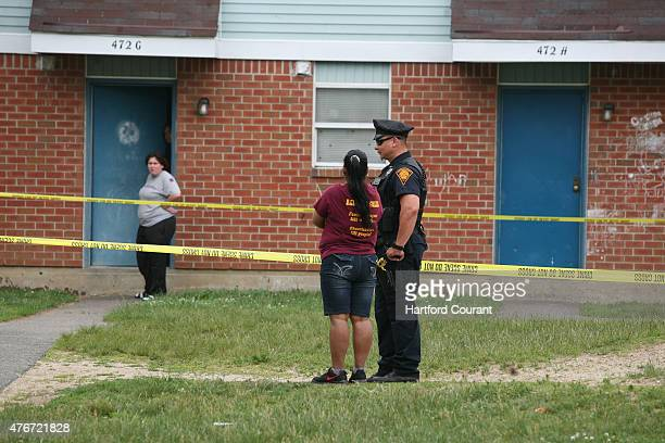 Marisel Arbelo speaks with an officer as police investigate the early morning shooting of nine people at the Trumbull Gardens housing complex in...