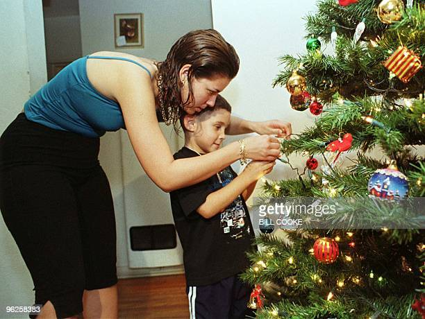 Marisleysis Gonzalez helps her cousin Elian Gonzalez decorate a Christmas tree at her home in Miami 22 December after finding out that immigration...