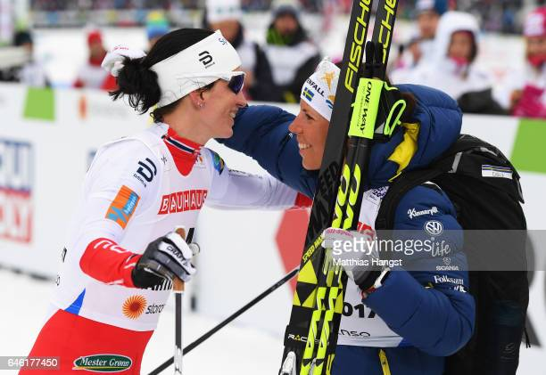 Marit Bjoergen of Norway celebrates after crossing the finish line with Charlotte Kalla of Sweden in the Women's 10km Cross Country during the FIS...