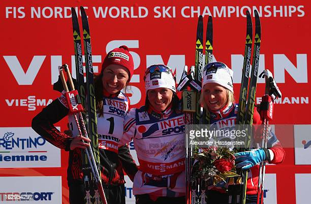 Marit Bjoergen of Norway celebrates First place on the podium with Second placed Justyna Kowalczyk of Poland and Third placed Therese Johaug of...